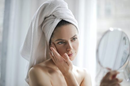 tender-woman-after-shower-examining-skin-with-mirror-3754678